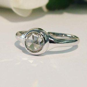 minimalist engagement ring with white gold bezel style setting
